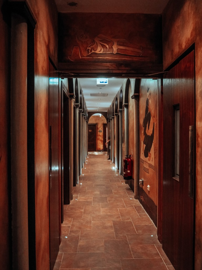 Corridor of dark wood paneling containing the treatment rooms at The Thai Spa in one of Ireland's most luxurious hotels.