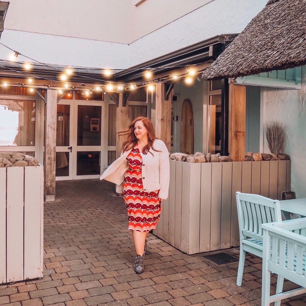 Woman walking through a seaside restaurant in County Clare Ireland with fairy lights twinkling overhead