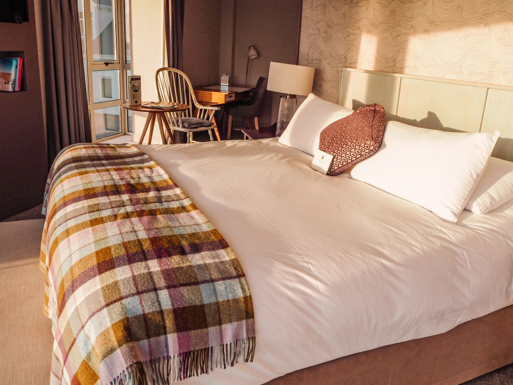 Large King size bed with tartan wool blanket at Armada Spanish Point Hotel