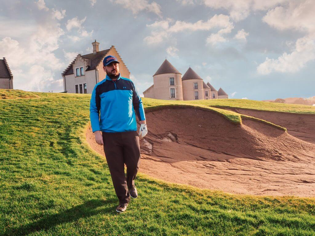 Male golfer in a blue top and black trousers standing in front of a golf bunker at Lough Erne Golf Resort.