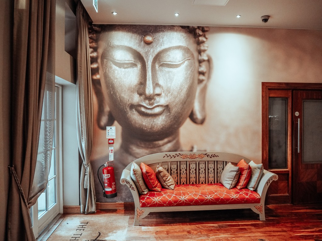 Thai spa at Lough Erne resort with a large mural of a buddha on the wall and a red couch to wait on.