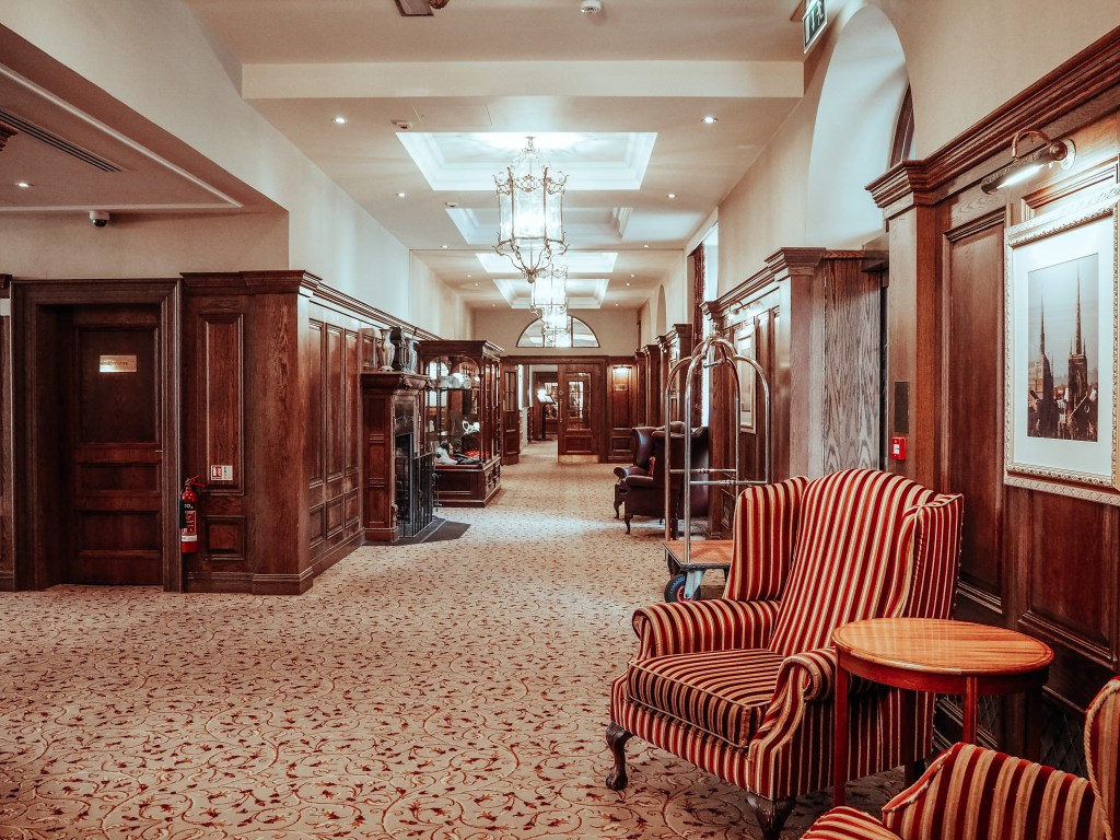 Reception area of a hotel with striped red and orange armchairs and wooden paneling on the walls