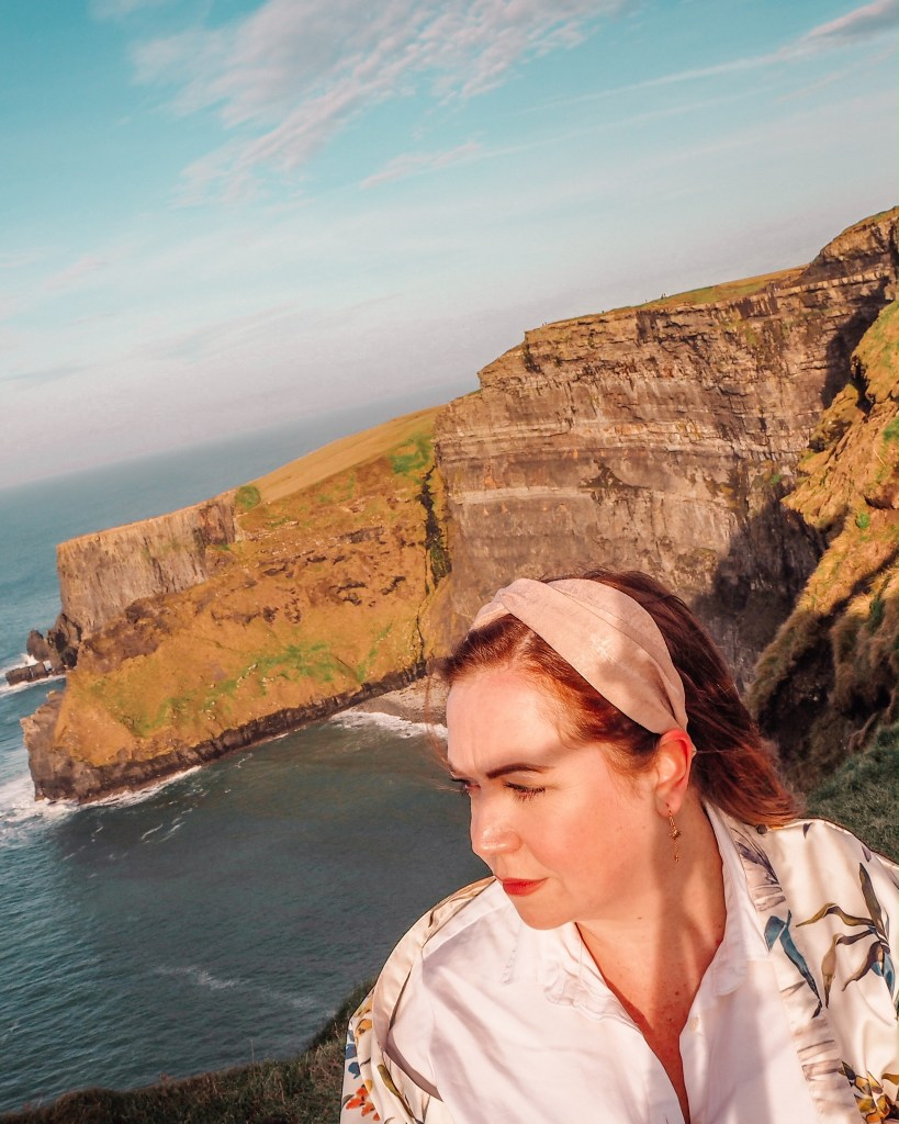 Woman with red hair watching the sunset at the Cliffs of Moher Ireland