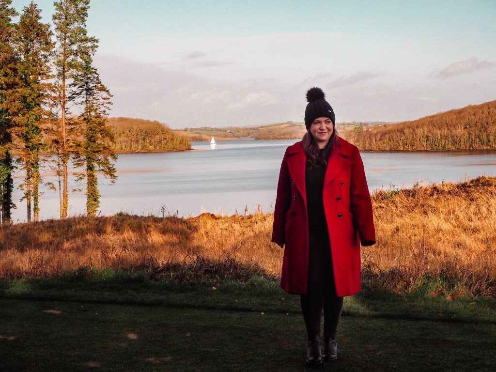 Woman in a red coat overlooking Lough Erne in Northern Ireland as a sailboat sails by.