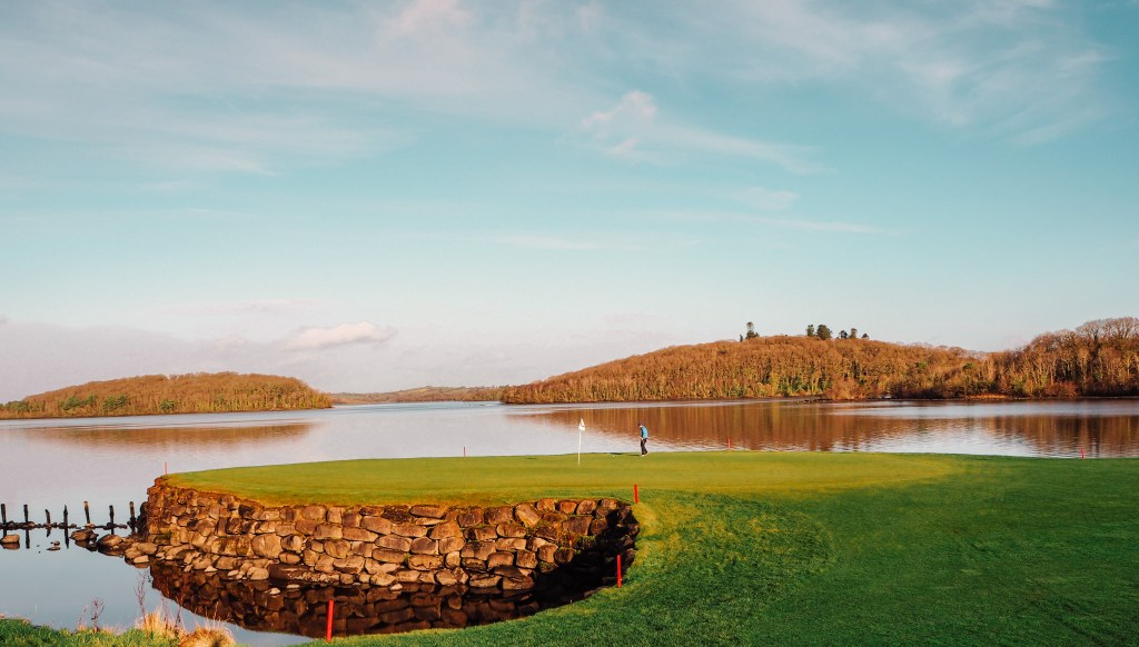 Male golfer playing the signature hole 10 at Lough Erne golf and spa resort.