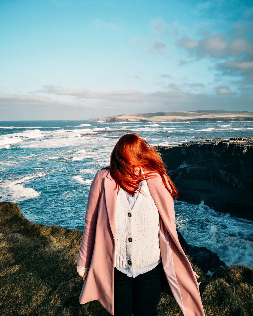Woman wearing a pink coat and an Aran sweater standing on a cliff edge with the wind blowing her red hair in her face.
