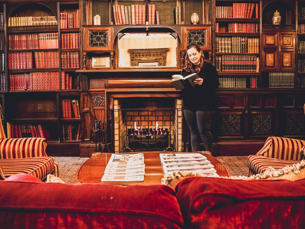 Female hotel guest reading in the library of Lough Erne resort.