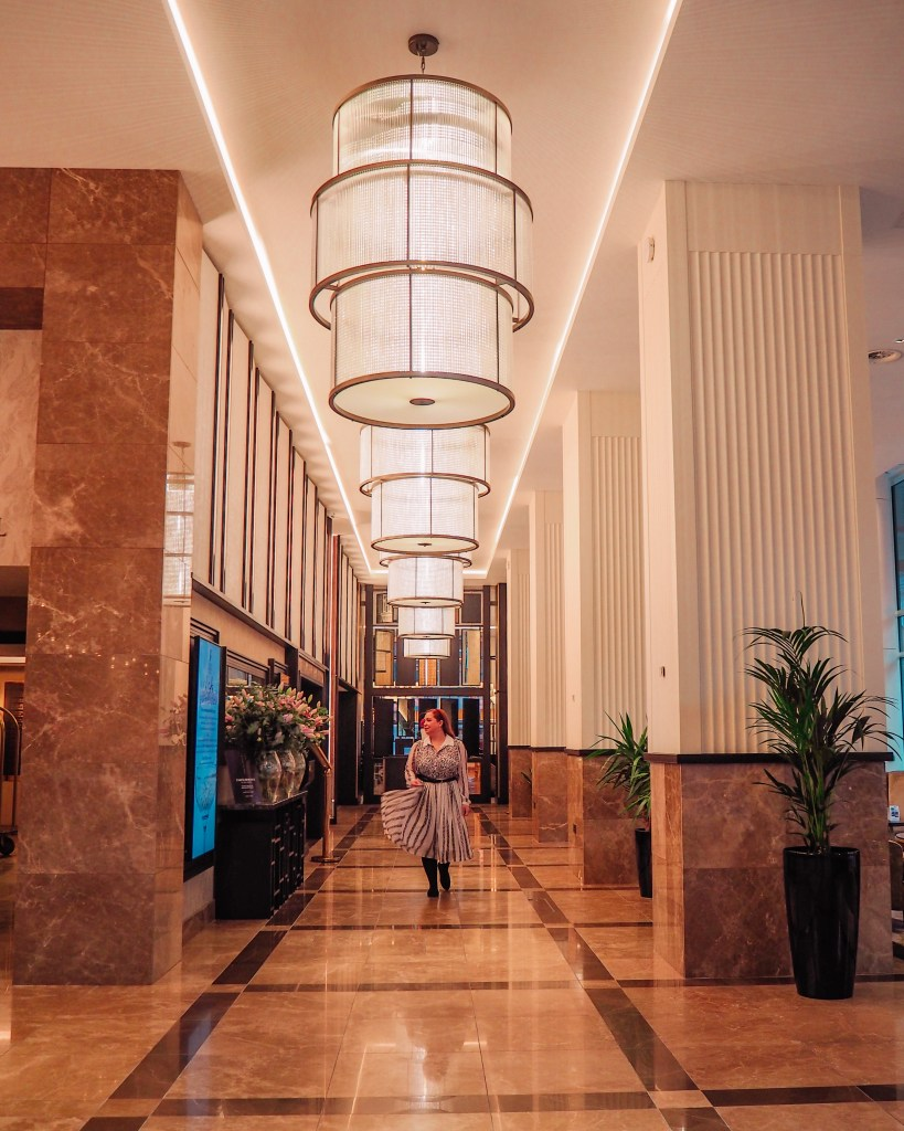Woman in a white dress walking through the reception hall at Grand Central Hotel Belfast an instagram spot belfast.