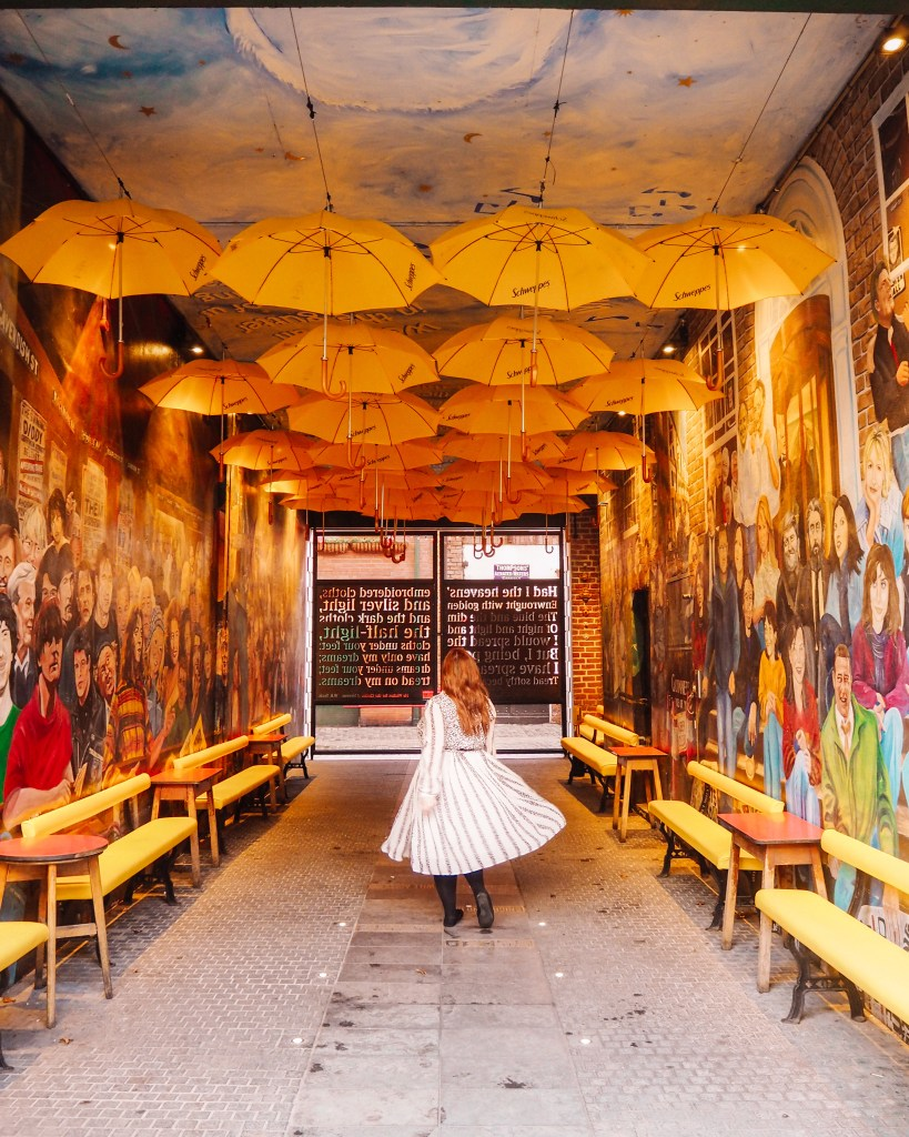 Woman in a white dress twirling under an umbrella sky in one of Belfast's best Instagram spots