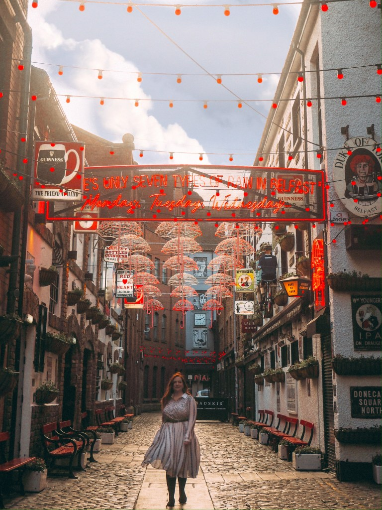 Woman in a white dress walking along the cobbled streets of the cathedral quarter in Belfast, beside the Duke of York pub an Instagram spot in Belfast