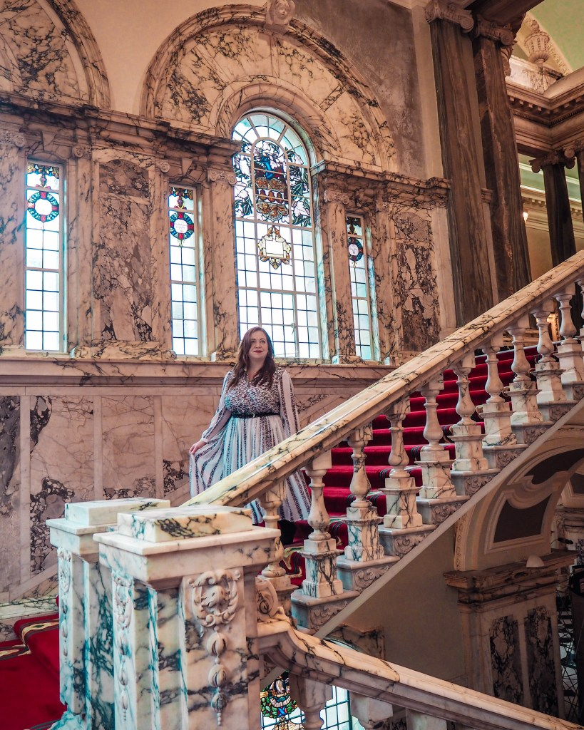 Woman in a white dress walking down the marbled staircase of Belfast City Hall