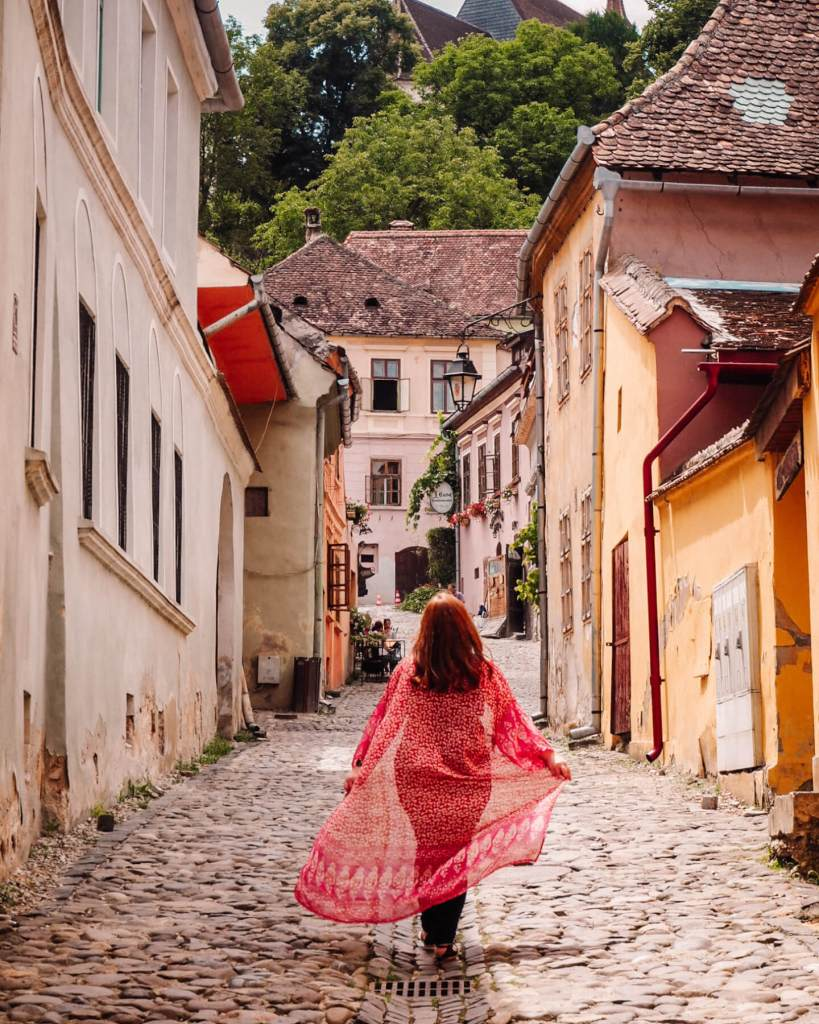 Woman walking around the colourful streets of Sighisoara Romania