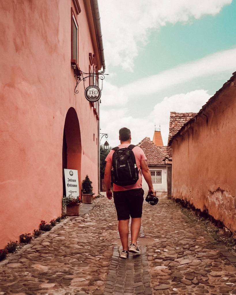 Man walking with his camera through the cobbled streets of Sighisoara Romania