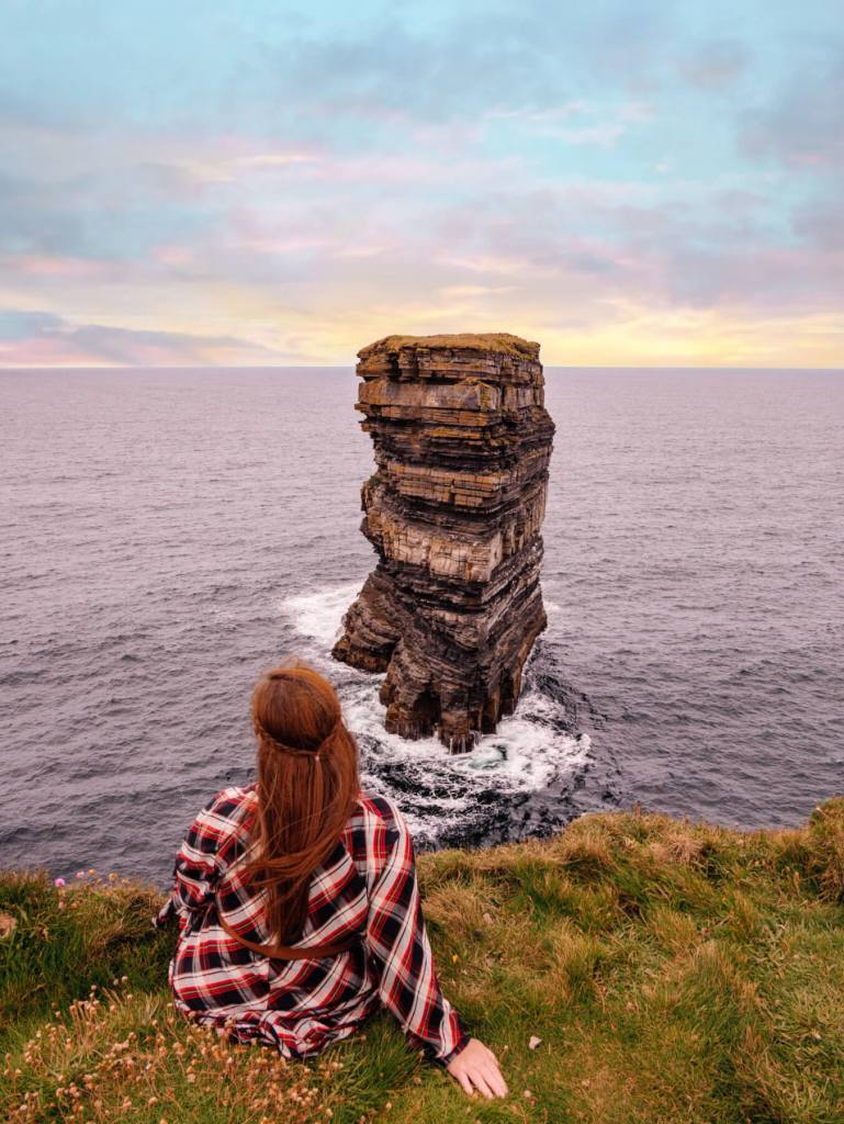 Woman in a tartan dress sitting at Downpatrick Head in county Mayo Ireland