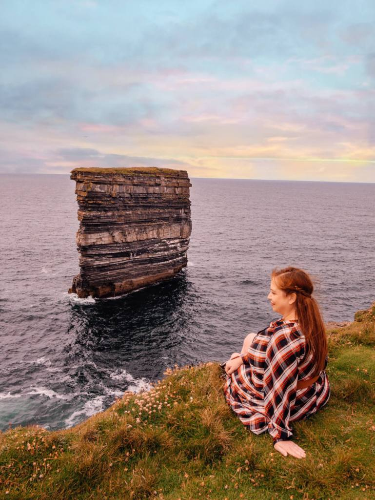 Woman sightseeing at Downpatrick Head in Ireland