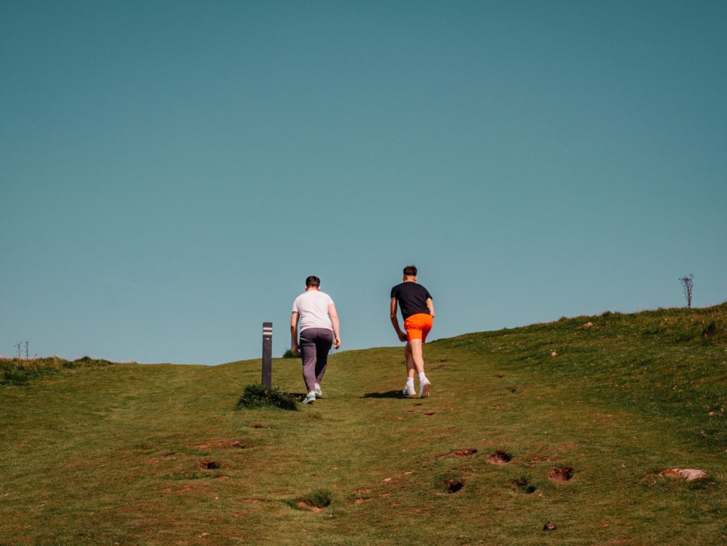 Two boys climbing up the steep incline at Loughcrew Cairns