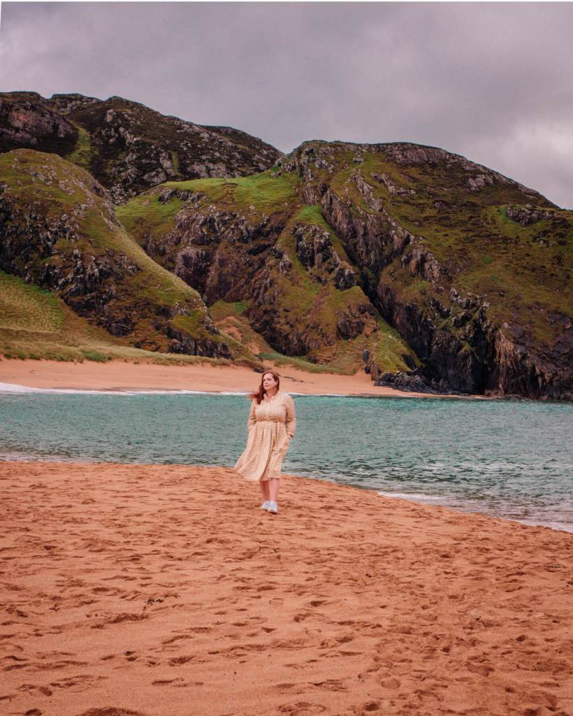 Woman walking on a beach in Donegal Ireland during her staycation in Ireland