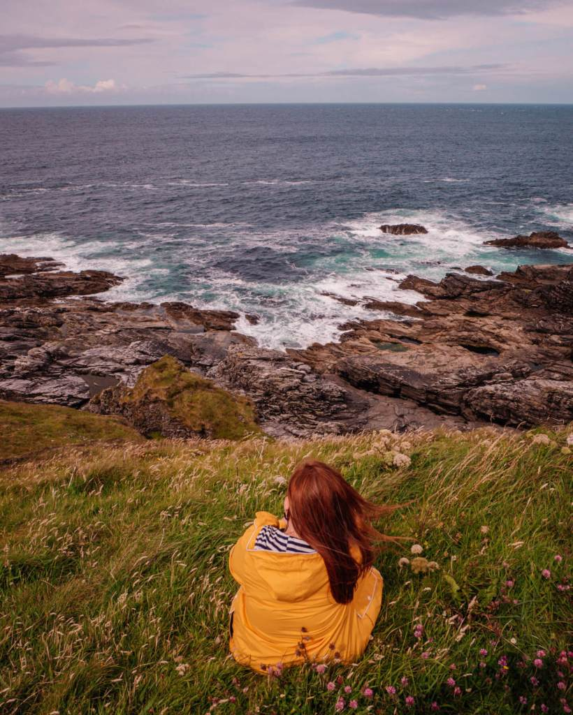 Woman in a yellow raincoat overlooking the cliffs at Malin Head in Donegal