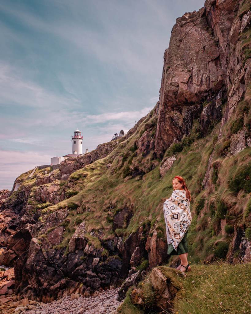 Irish woman with red hair standing on rocks at Fanad Head Lighthouse in County Donegal Ireland