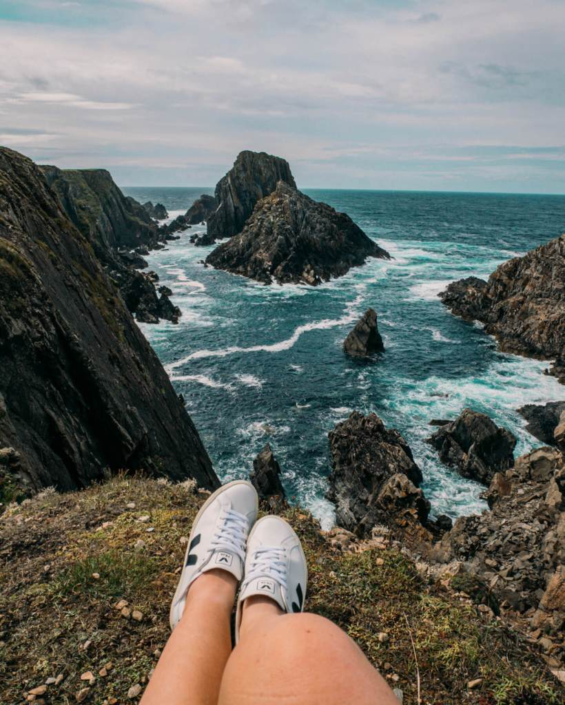woman's feet with a background view of Malin Head in Donegal Ireland