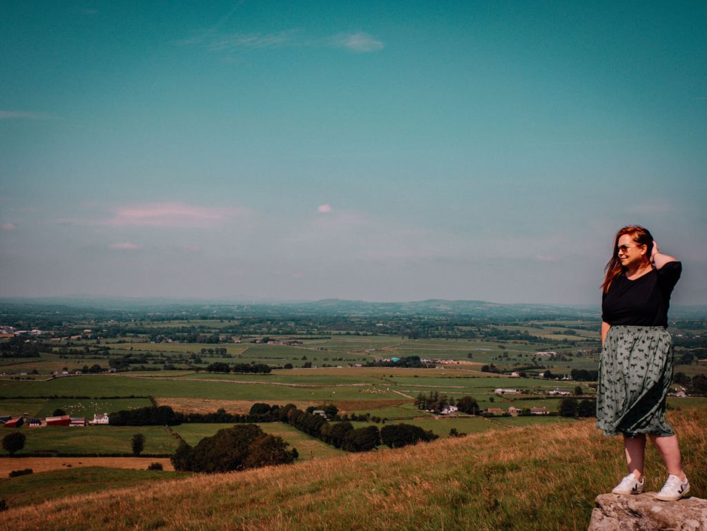 Woman in a green skirt looking out over the views at Loughcrew Cairns in Ireland