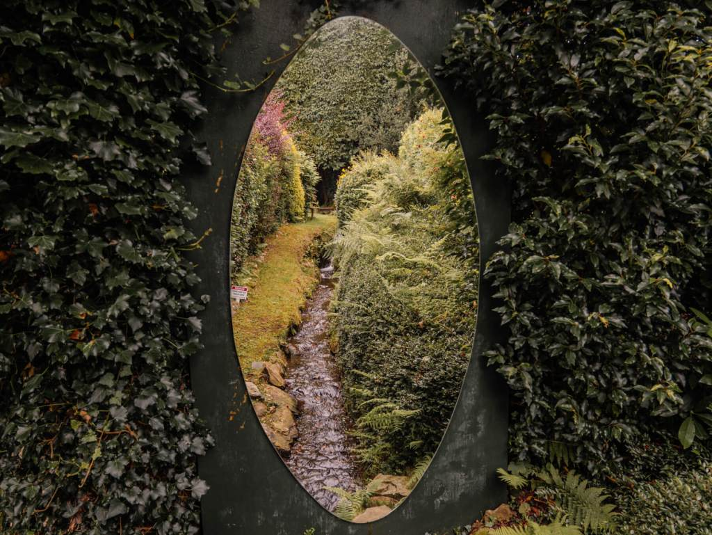 Mirror reflecting a beautiful stream at Shekina Sculpture Garden in Wicklow Ireland
