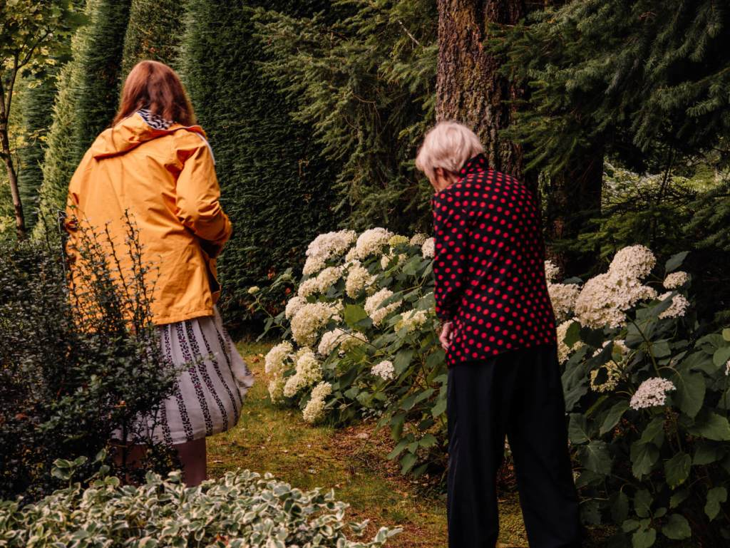 Elderly woman showing a younger woman in a yellow raincoat around Shekina Sculpture Garden in Wicklow Ireland