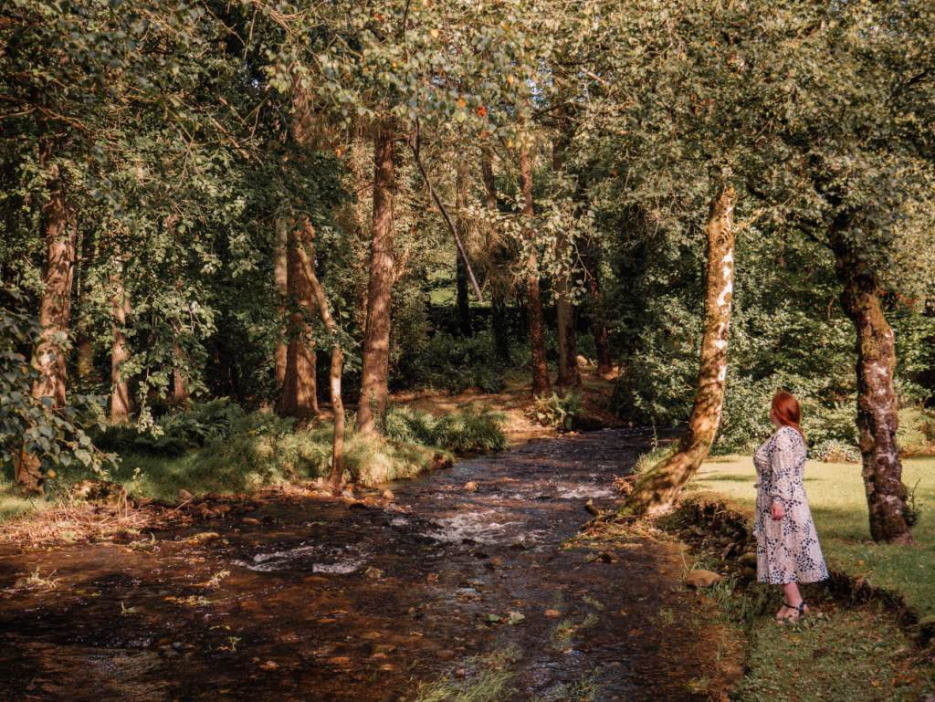 Woman walking beside a brook at Brooklodge Hotel in Wicklow
