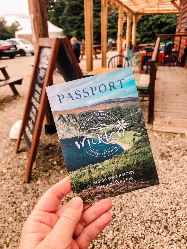 Woman holding the Wicklow Passport, a great way to explore Wicklow on your staycation Ireland