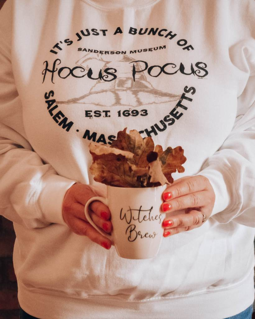 Woman holding a cup that say witches brew with fall leaves and wearing a hocus pocus sweater for an Instagram photo