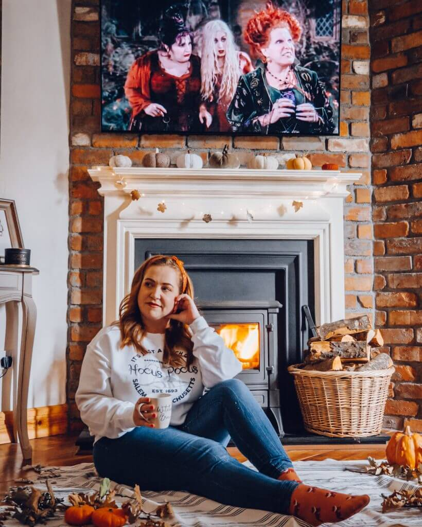 Woman sitting in front of a fire surrounded by pumpkins posing for a Halloween Instagram photo