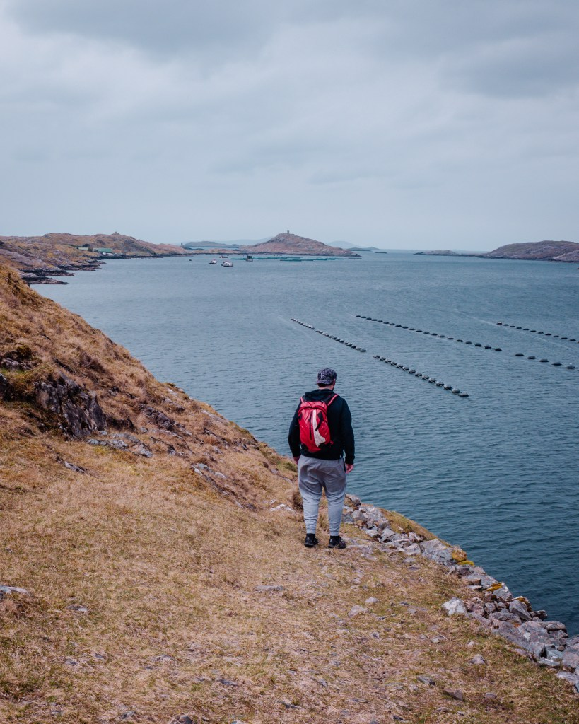 Man in a grey tracksuit and red backpack walking along the edge of Killary Harbour on a Connemara hike