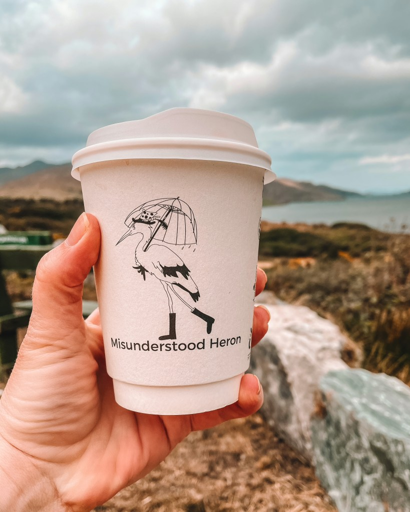 Hand holding a coffee cup from Misunderstood Heron over views of Connemara Ireland