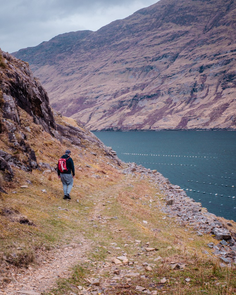 Man in a grey tracksuit and red backpack walking along a rocky mountain path on the Killary harbour coastal walk on a connemara hike