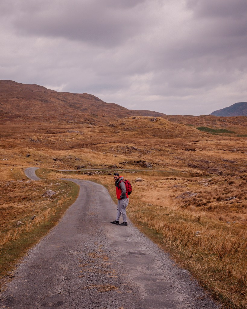 Man in a grey tracksuit and red rain jacket hiking on a walking trail in Connemara Ireland