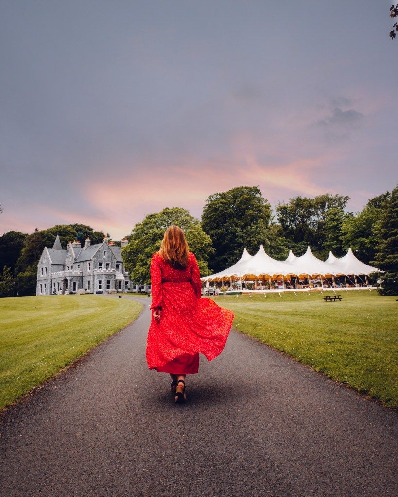 Woman in a red dress walking up to the manor house at Mount Falcon