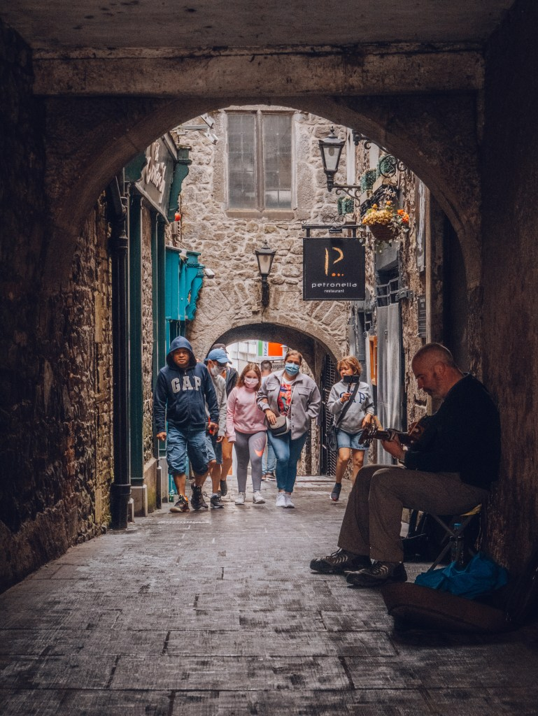 Narrow streets of Kilkenny Ireland with a busker playing a guitar on it