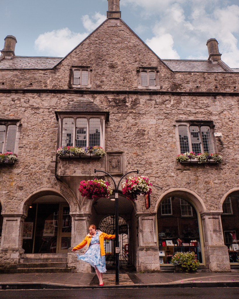Woman in a yellow raincoat twirling around a lamp post outside Rothe House in Kilkenny Ireland