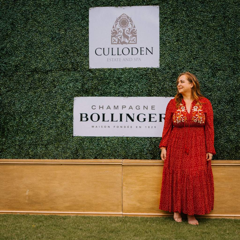 Woman in a red dress standing at a Bollinger Champagne ivy wall at the art & soul art exhibition at Culloden Estate