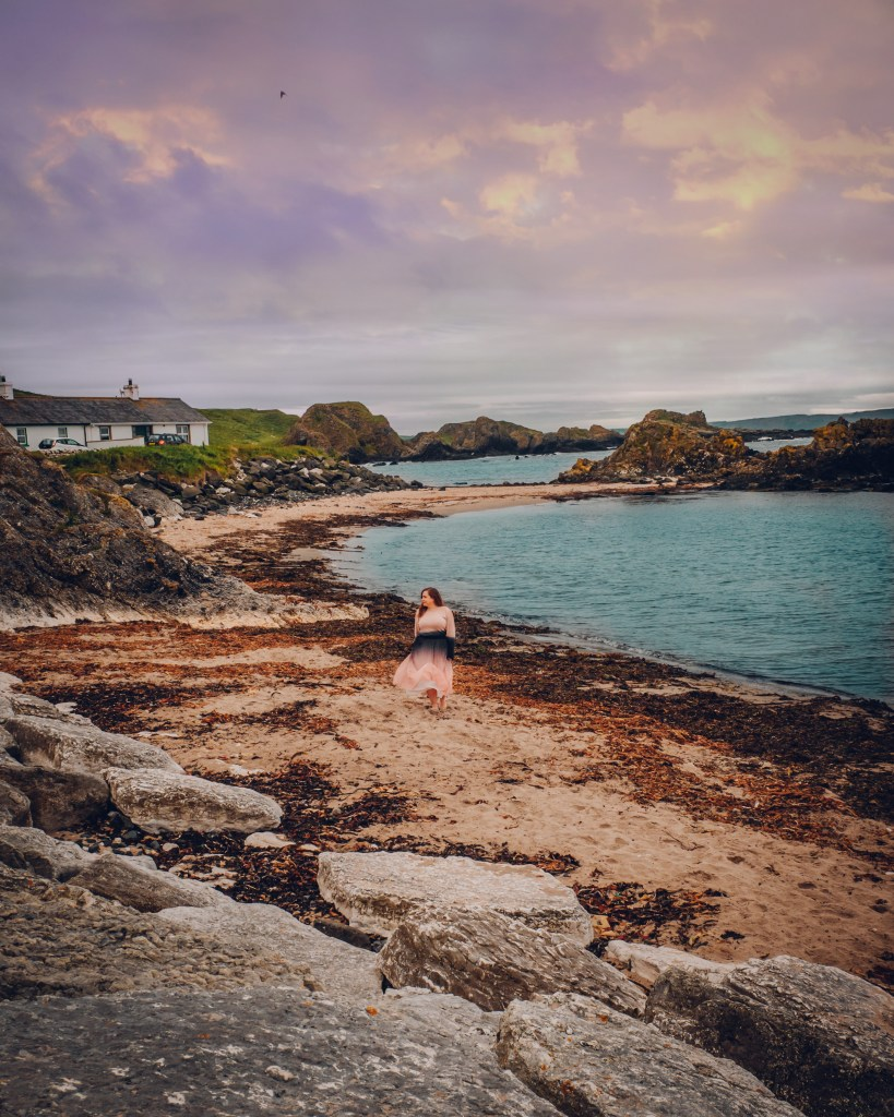 Woman in a pink dress walking barefoot on the beach at Ballintoy Harbour