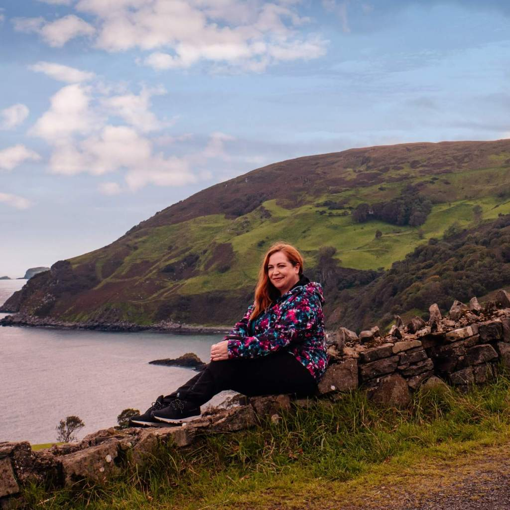 Woman sitting on a stone wall overlooking dramatic scenery at Murlough Bay known as Slavers Bay in Game of Thrones