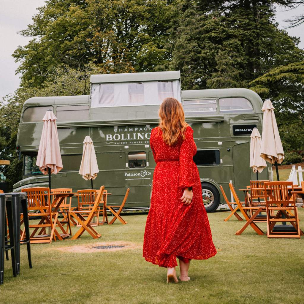 Woman in a red dress walking towards the Bollinger Bus at Culloden Estate to get champagne