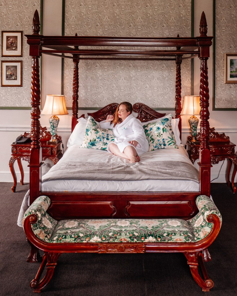 Woman lying on a four poster bed in a manor room at the Lyrath Estate and spa on a weekend in Kilkenny