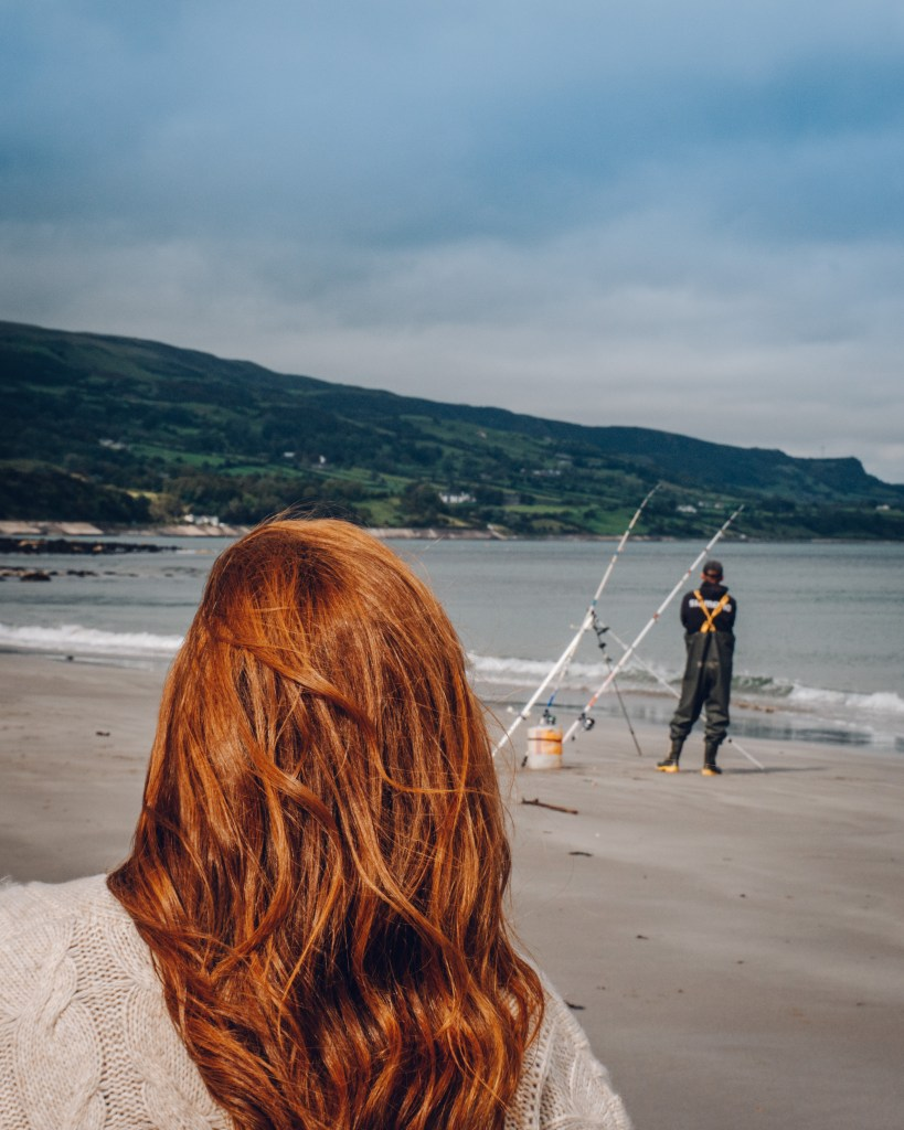 Woman with red hair watching a man fishing on the beach at Ballygally in County Antrim Northern Ireland