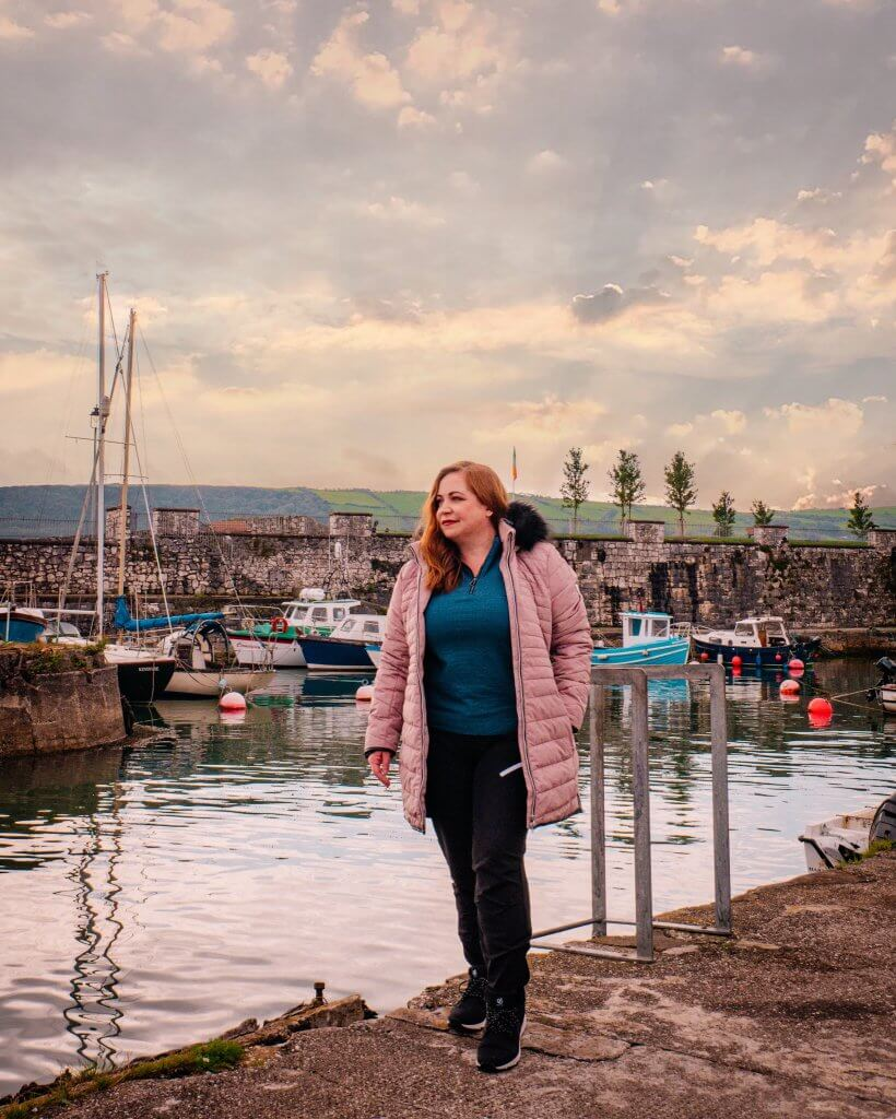 Woman in a pink coat standing at Carnlough Harbour