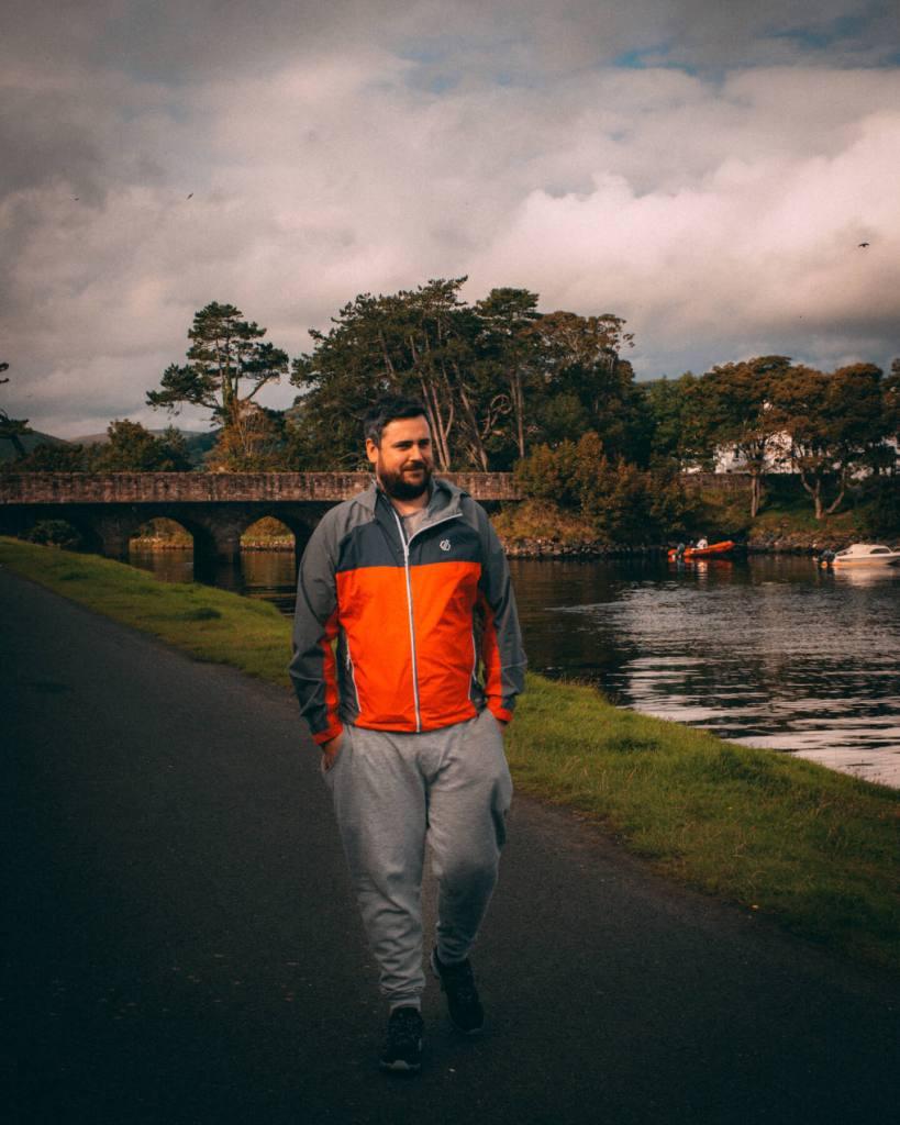 Man in an orange jacket walking along the harbour at Cushendun in Antrim Northern Ireland
