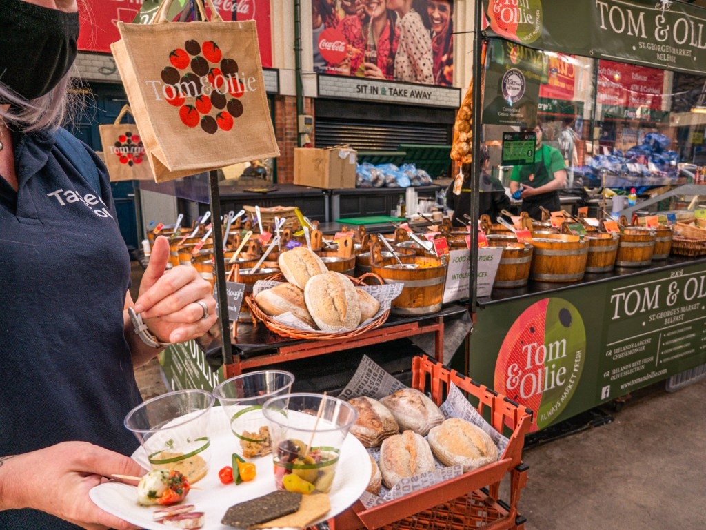 People sampling food at a market stall on a walking tour of Belfast