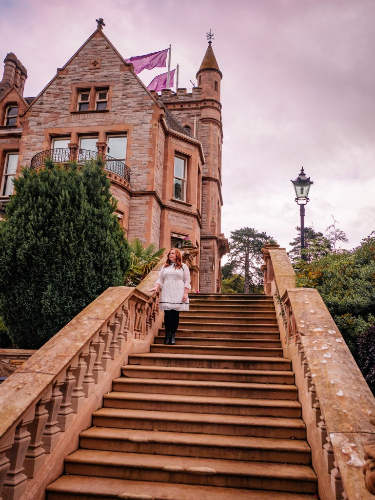 Woman standing on the steps of the five star Culloden Estate and Spa