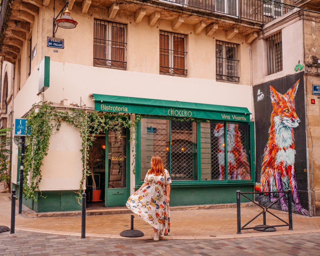 Woman walking in front of a restaurant and fox mural in Bordeaux France