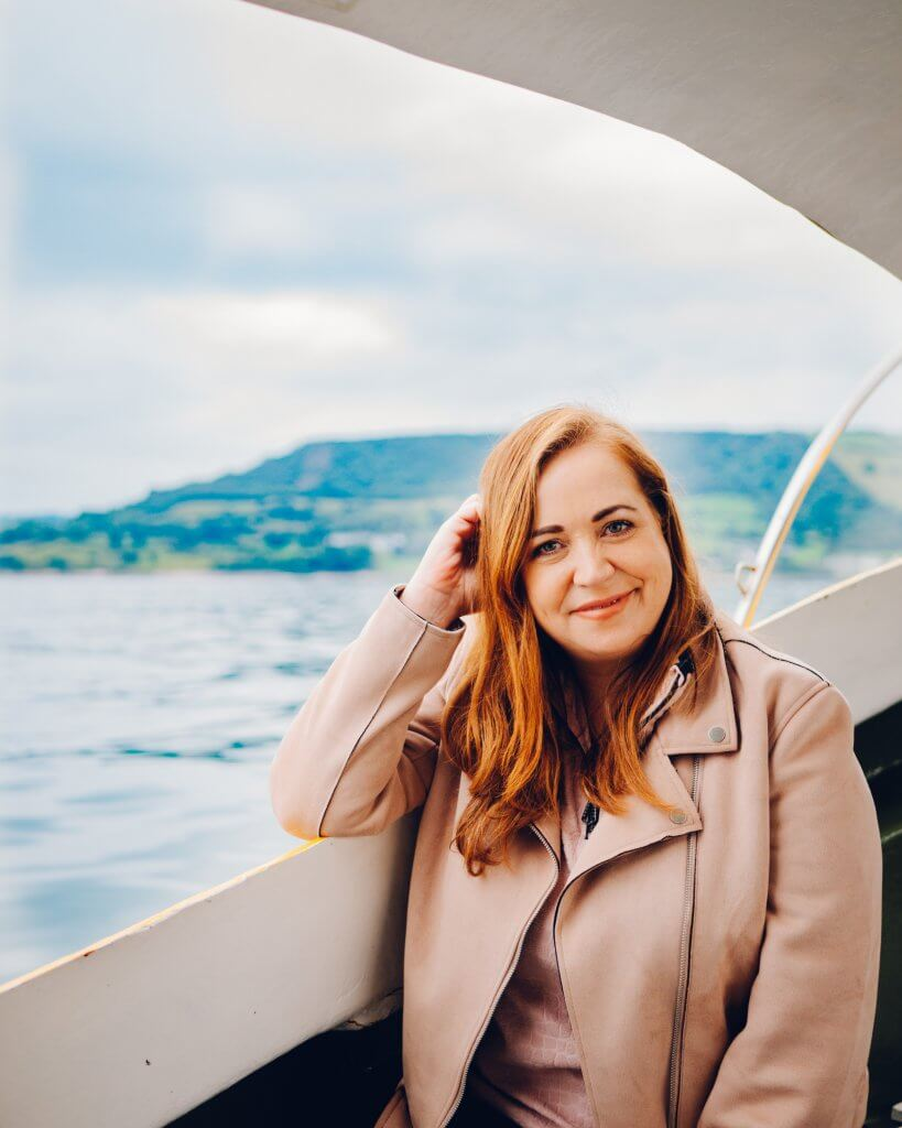 Woman sitting on a boat in Carnlough Harbour in Antrim Northern Ireland